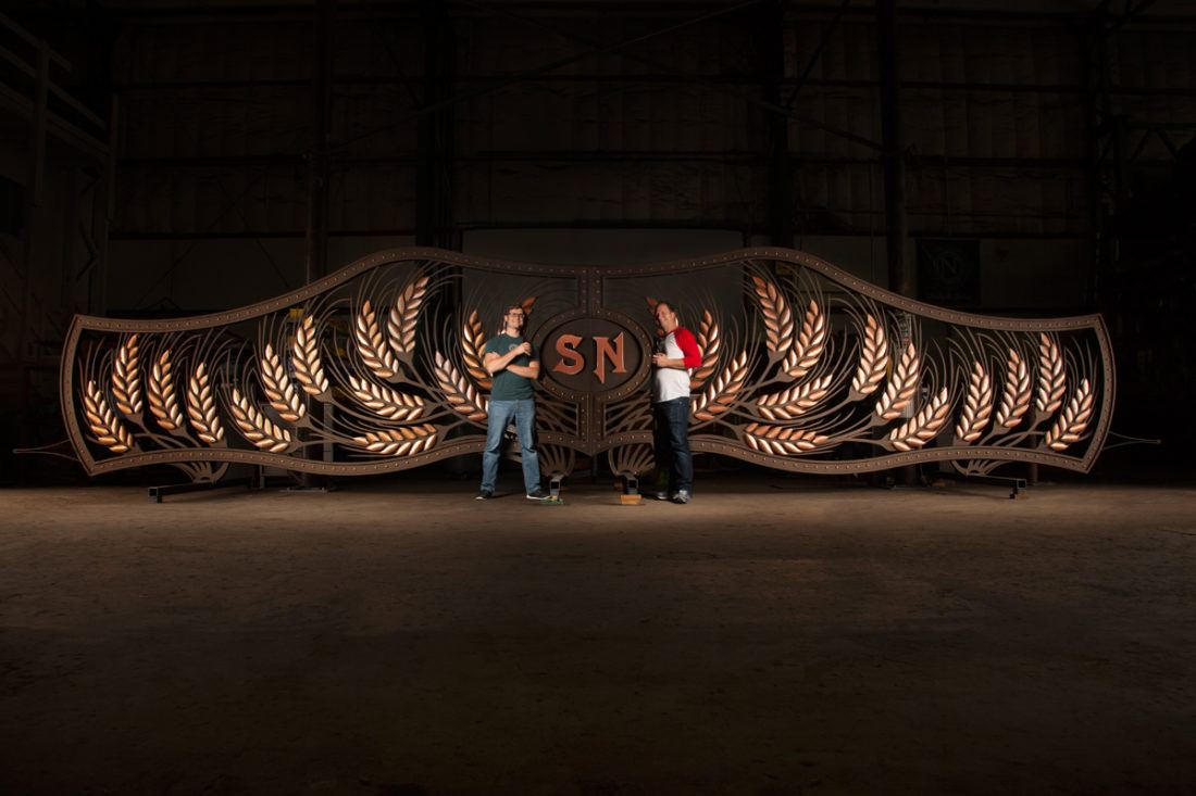 Owners of Ninkasi Brewing Company pose with custom fabricated entry gate
