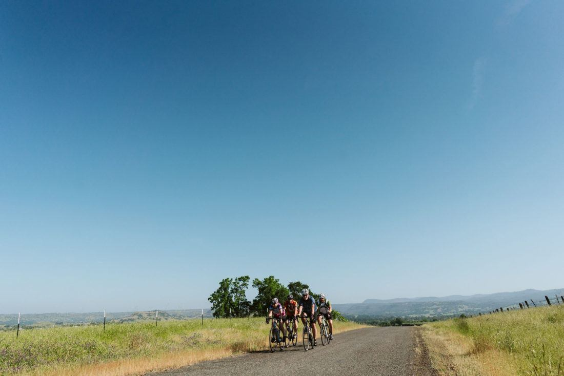 Group of cyclists riding with deep blue sky beyond
