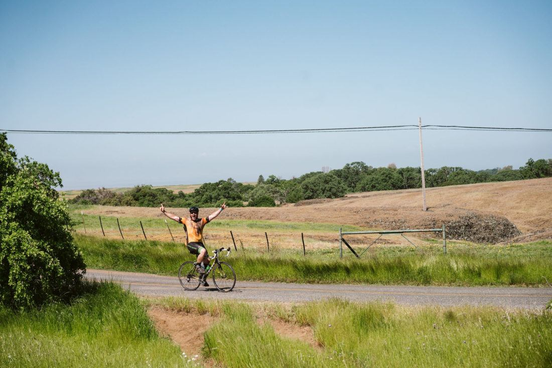 Cyclist climbing road flanked by expansive grassland