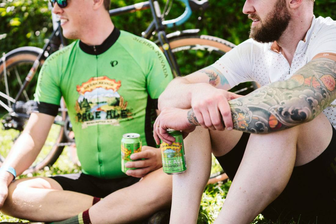 Two cyclists talking and holding Sierra Nevada beers