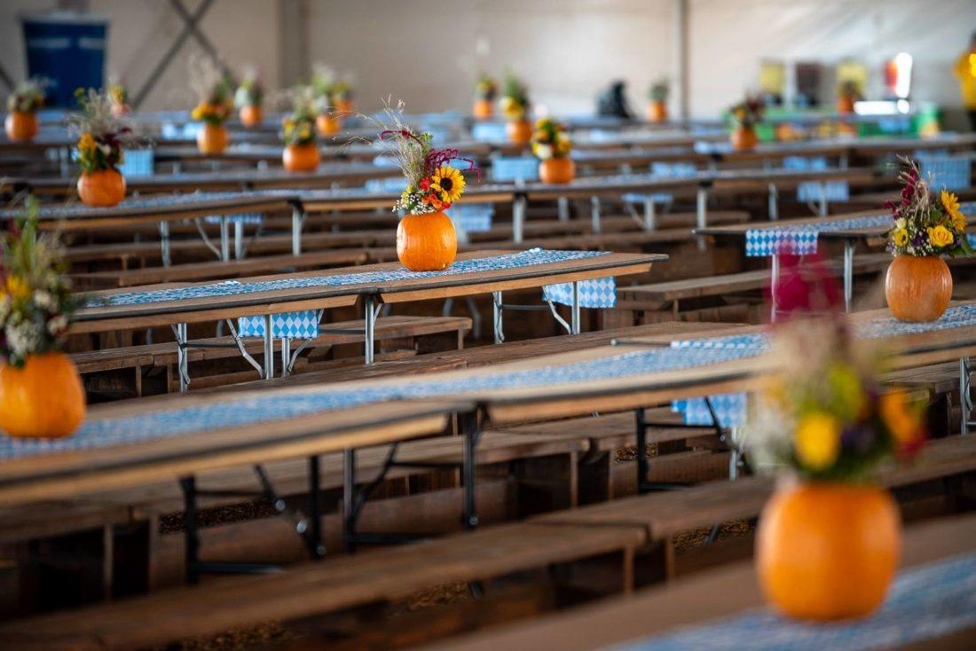 Tables topped with flower-filled pumpkin centerpieces