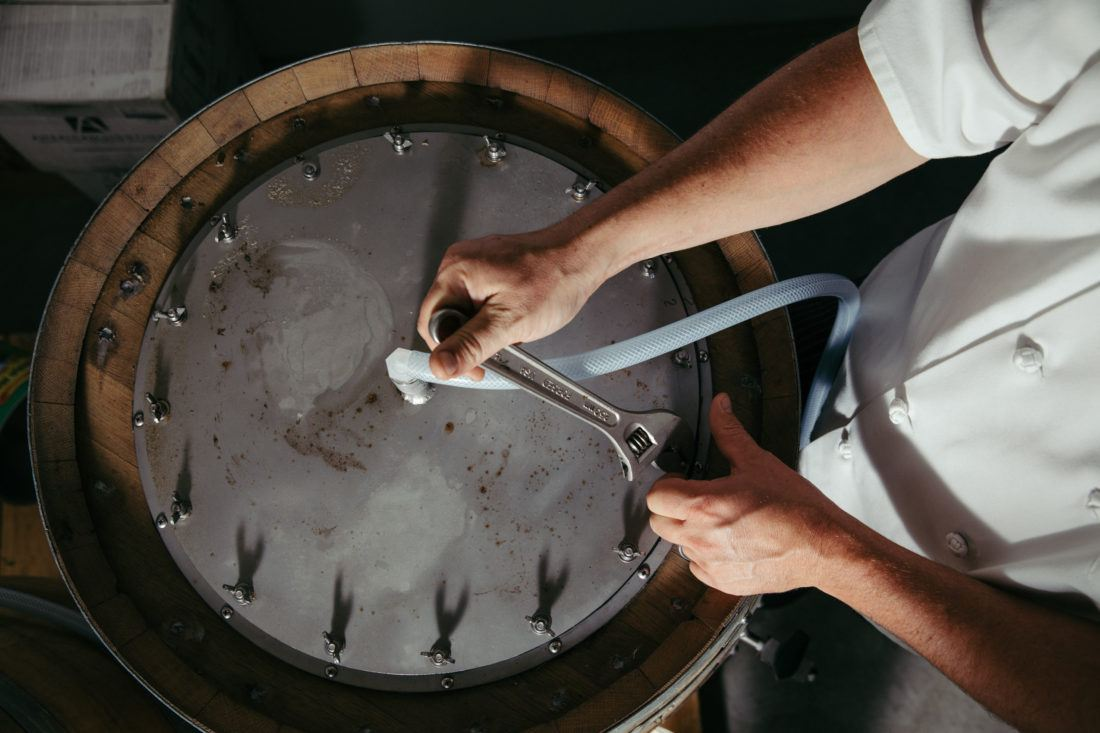 Hands removing the lid of a beer barrel that's aging sauerkraut