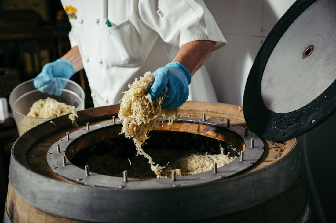A chef pulling a handful of sauerkraut out of a beer barrel