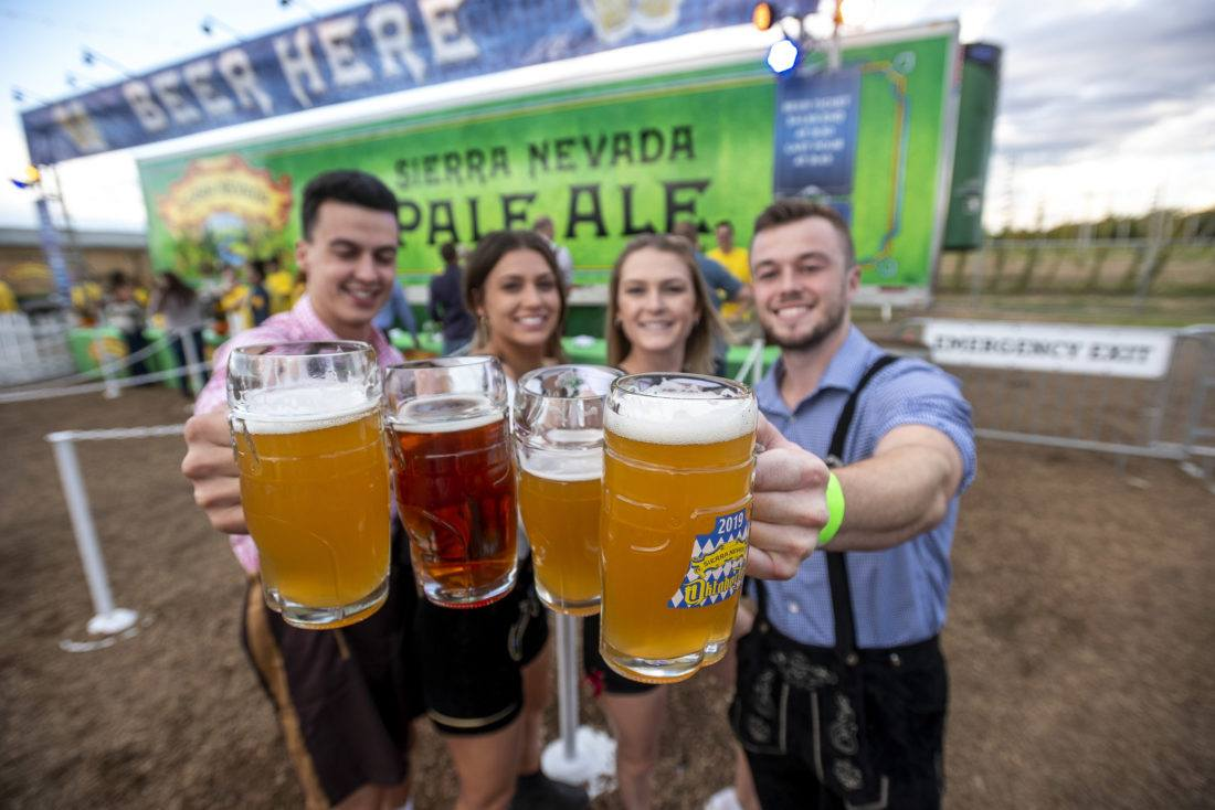 Group of people raising steins of beer at Sierra Nevada Brewing Company's Oktoberfest party