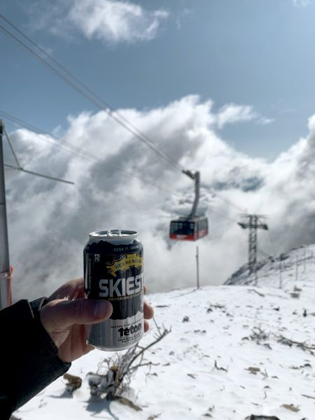 Holding can of Skiesta by ski lift