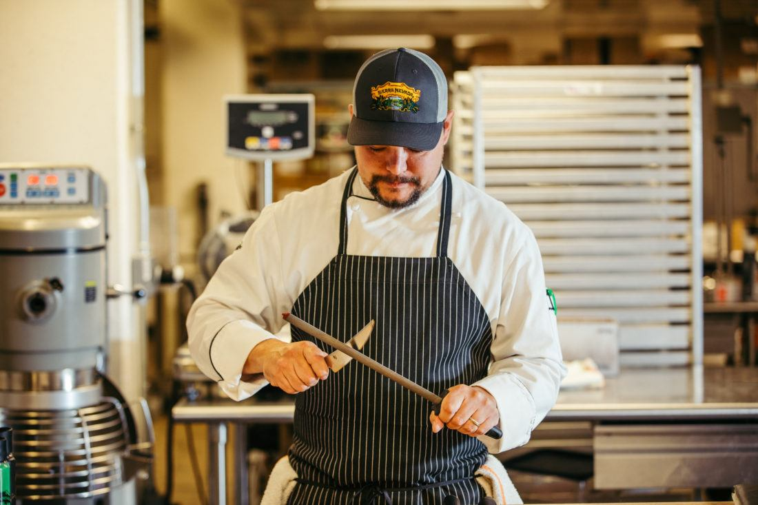 Male employee in restaurant kitchen sharpening knives