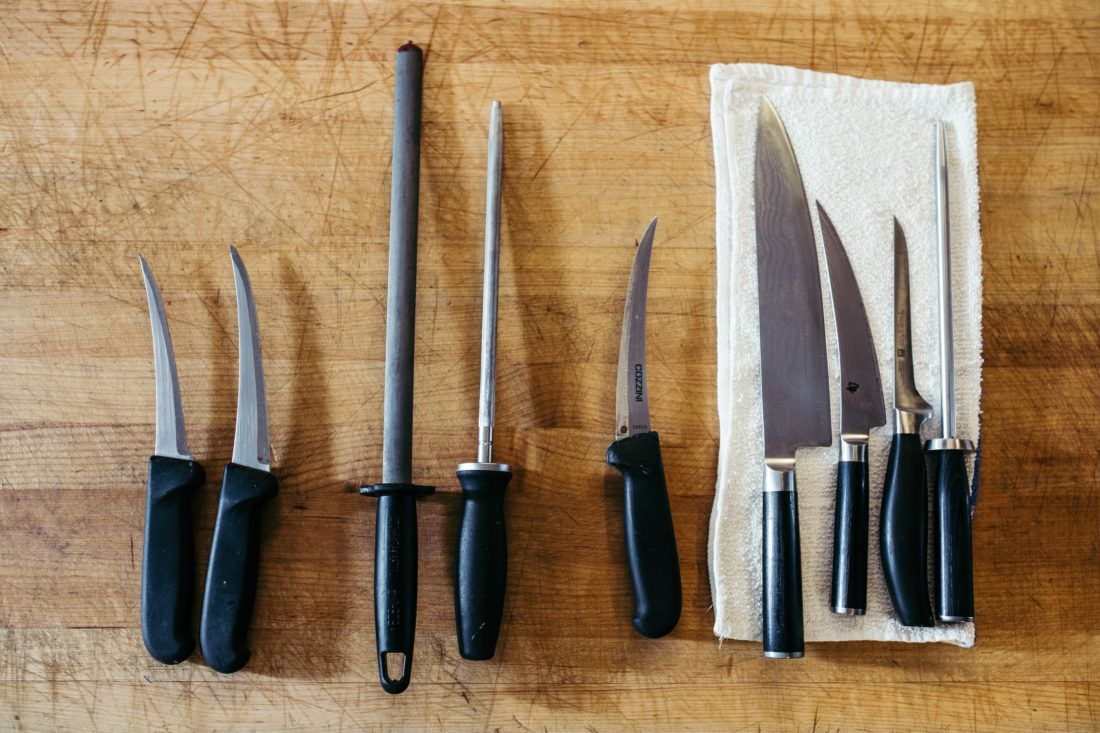 Lineup of kitchen knives on butcher block countertop