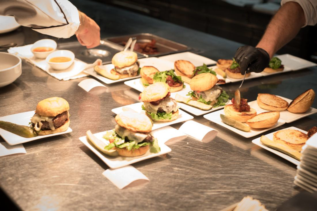 Assembly line of hamburgers in restaurant kitchen