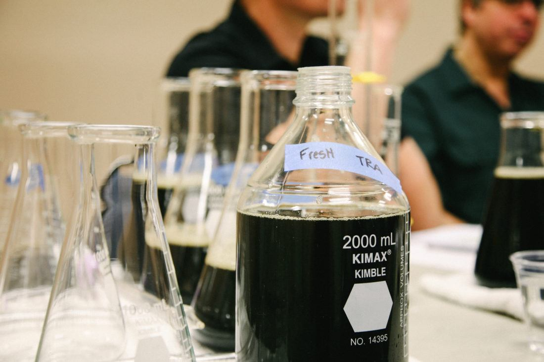 A lineup of several beakers filled with dark beer