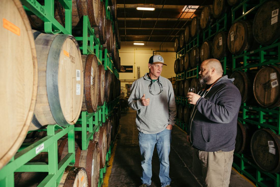 Two Sierra Nevada brewers talking next to stacks of wooden barrels