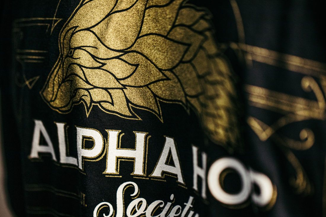 Close up of Alpha Hop Society T-shirt with black, white, and shimmering gold