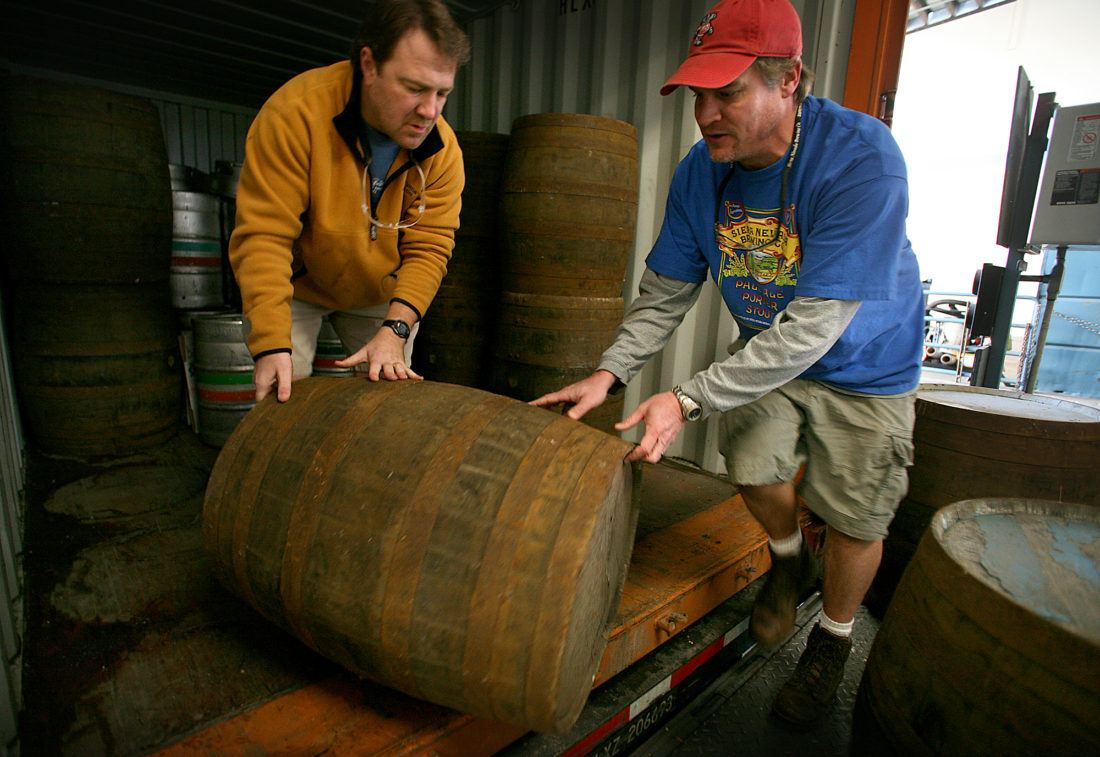 Two male brewers rolling a wooden barrel out of a delivery truck