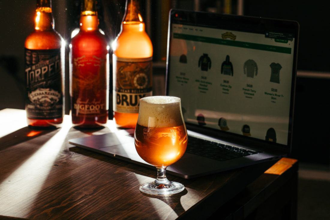 Sun rays shining through several bottles of Sierra Nevada Brewing Company beer and a laptop computer