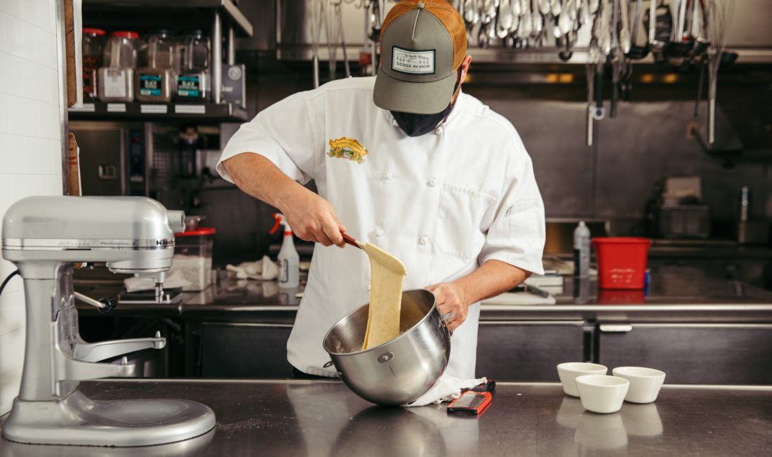 Male chef mixing batter for spaetzle pasta noodle dish