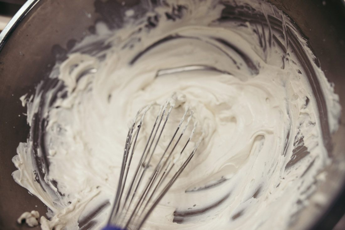 Whisking homemade whipped cream in metal bowl