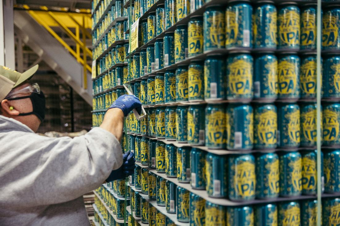 A Sierra Nevada employee cuts polyester strapping off a stack of Hazy Little Thing IPA cans