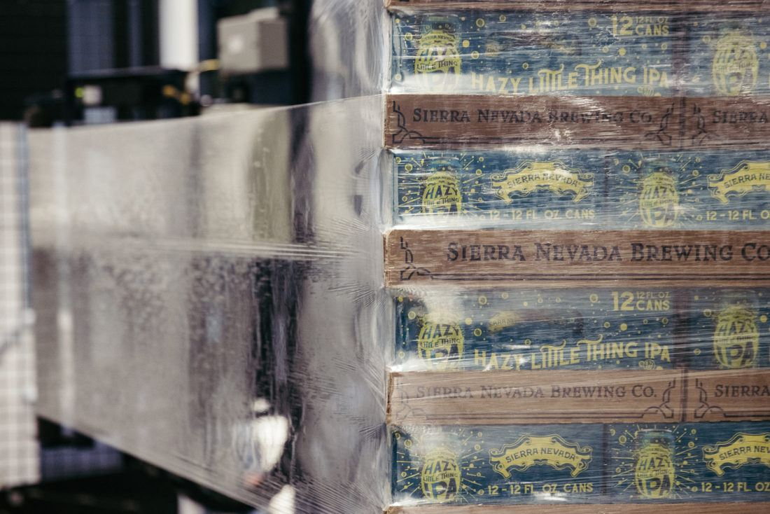 A machine stretches shrink wrap around a stack of Hazy Little Thing IPA 12-packs