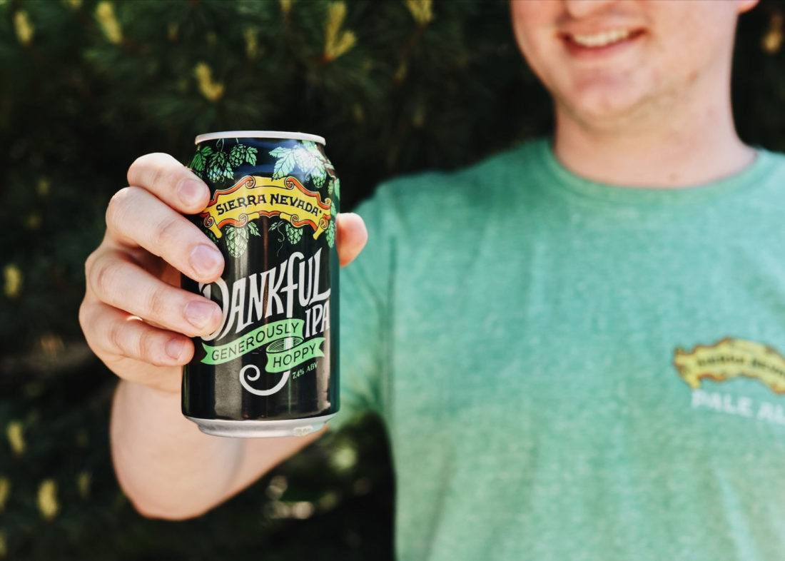 A young man holding out a can of Sierra Nevada Dankful IPA.