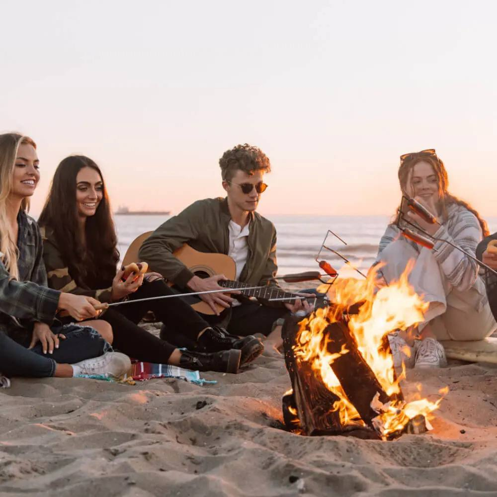 Group of 4 people around a campfire while one plays the guitar
