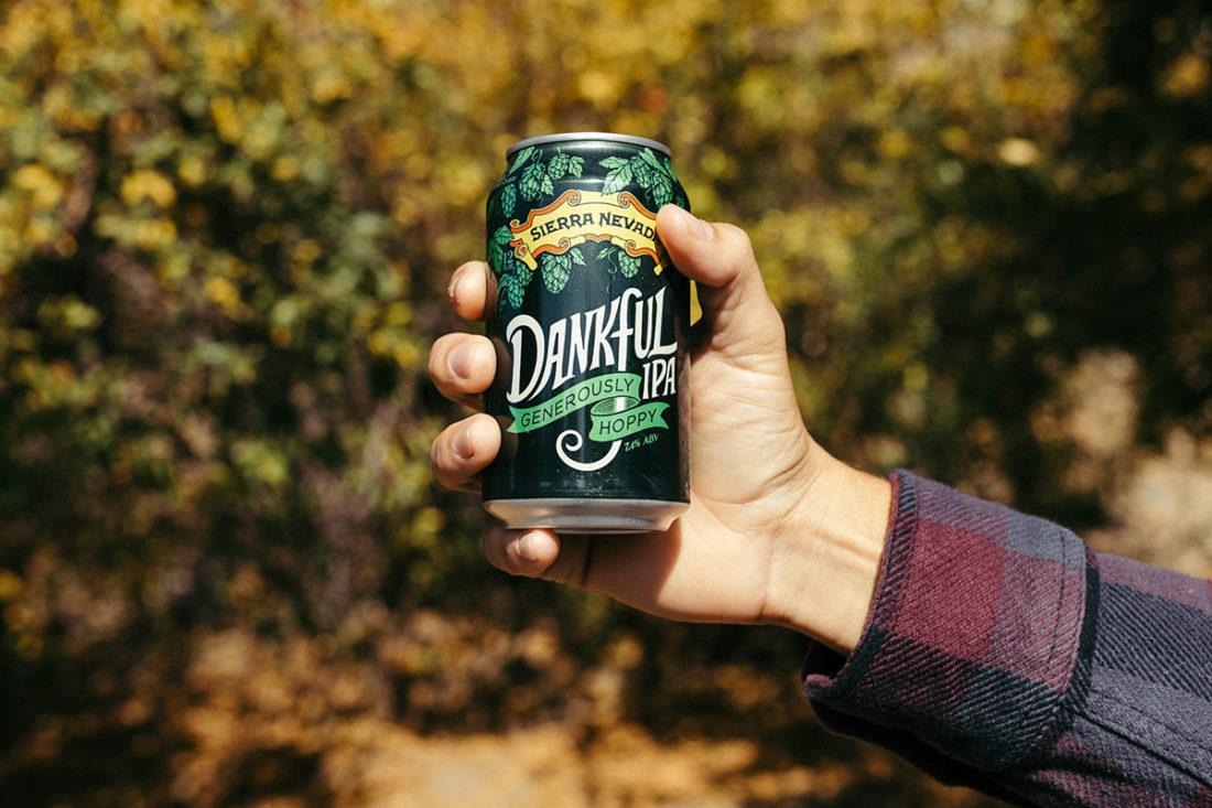 A hand holding a can of Dankful IPA amidst fall foliage