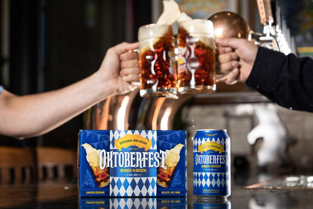 Two clinking steins of beer above a six-pack of Sierra Nevada Oktoberfest
