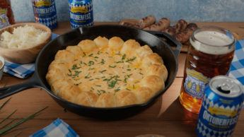 A cast-iron skillet filled with pretzel rolls and beer cheese.