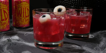 Cans of Wild Little Thing beer next to two glasses of Halloween punch
