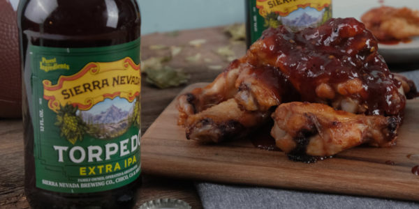 A bottle of Sierra Nevada Torpedo IPA next to a stack of maple bourbon wings